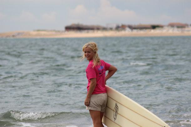Juliet walking with surfboard to sea