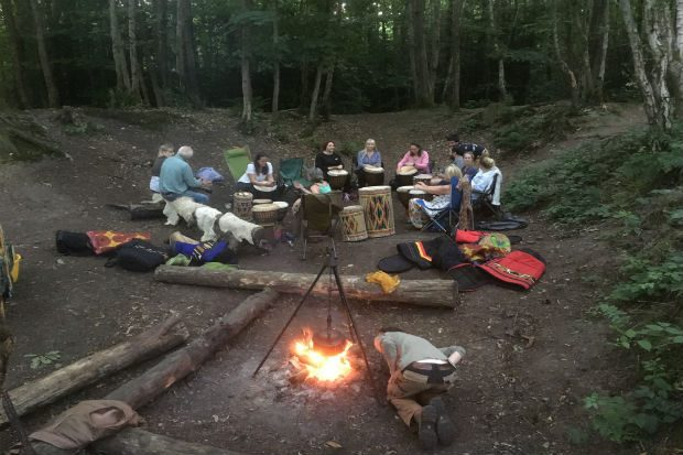 A group of people sitting in a circle in a forest with a burning stove beside them