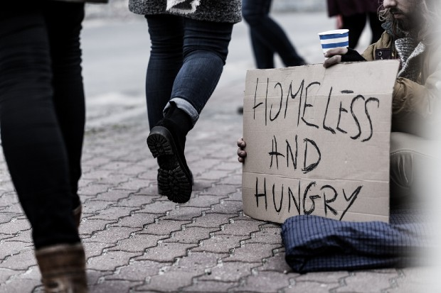 People walking passed a homeless person who is begging and in need of food