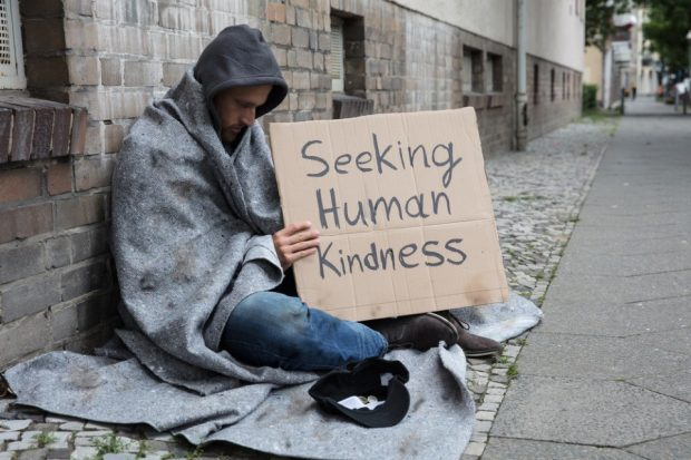 Man begging on the street - seeking human kindness