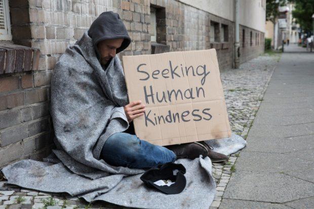 Man begging on the street - seeking human kindness
