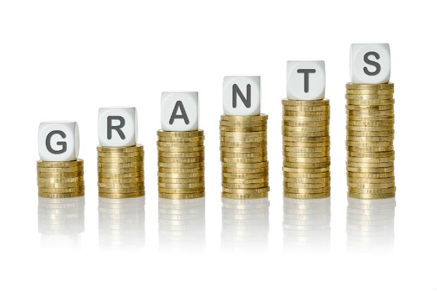 piles of coins with letters on each one to form the word grants