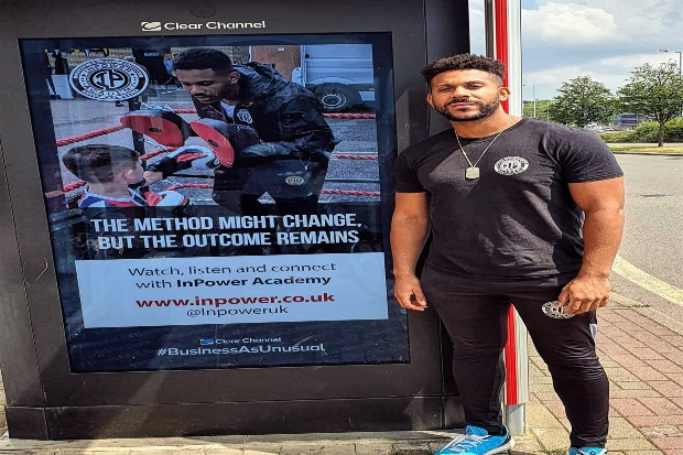 Daryl standing by a billboard with the slogan 'The method might change but the outcome remains'